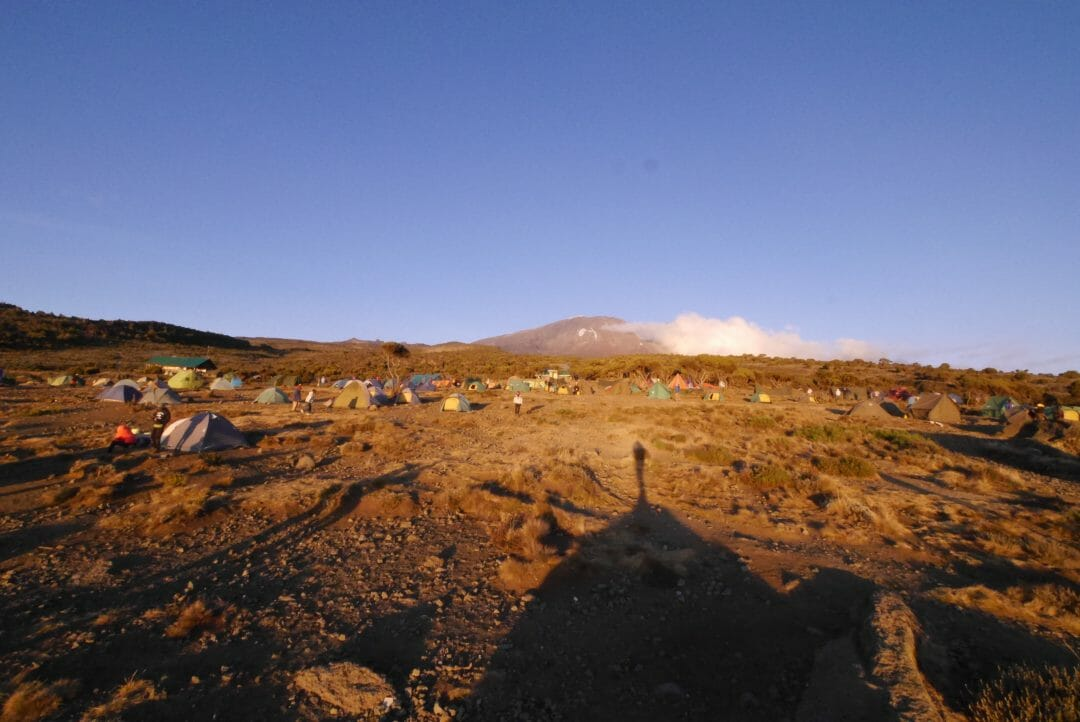 The red glow of the setting sun over camp as the cloud melts away from Kibo peak